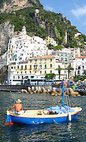 A small boat delivers water to the town of Amalfi, Italy.