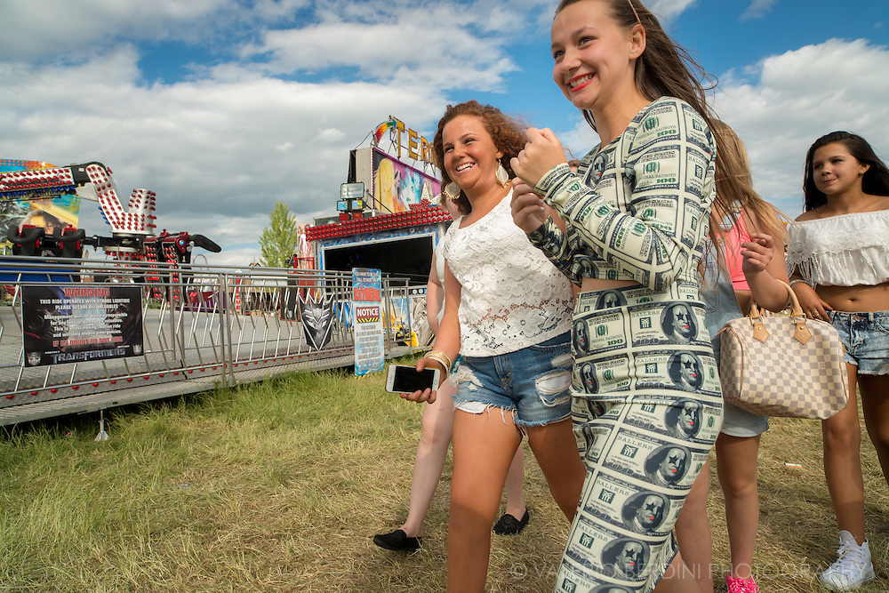 Money's too tight (to mention). A girl wanders with friends in a dress made of fake dollars.