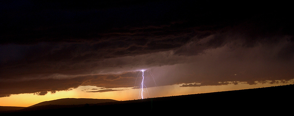 A fine art photograph of a lightning strike at sunset over El Rio Grande del Norte National Monument. New Mexico. USA.<br /> <br /> AVAILABLE AS:<br /> <br /> Size 12&rdquo; x 36&rdquo; (30.48cm x 91.44cm approx)*<br /> Edition of ONLY 100 at this size.<br /> US$450 + shipping<br /> <br /> Hand printed in Taos, New Mexico, USA by Taos Print and Photography Services using archival inks and fine art paper. signed and numbered by hand.<br /> <br /> Contact jim@jimodonnellphotography.com to order