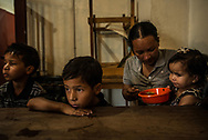 "LOS TEQUES, VENEZUELA - SEPTEMBER 22, 2017: Oriana Caraballo, 29, feeds her children Brayner, 8, Rayman, 6, and Sofia, 22 months, at a soup kitchen run the Nuestra Señora del Carmen church. They came for the first time after having nothing to eat for three days, except for water. Before the crisis, Ms. Caraballo did not struggle to feed her children with her wages from her job at a restaurant. However, for the past two years, it has been increasingly difficult for her to buy the food she needs for her family. She wept as she explained how her children foiled her in an attempt to commit suicide. Ms. Caraballo had decided that she to preferred to die, to be able to escape the immense pain of helplessly watching her children go hungry. She took them outside, while her baby daughter was sleeping - then came back inside and shut the door. She hung a cable from the ceiling of the house, and wrapped it around her neck. When she was just about to hang herself, she heard daughter start to cry. ""I heard a voice tell me: do it, do it, do it,"" she said. ""Then in my other ear I heard: don't do it, don't do it - look at your children."" Her son called to her, saying: ""Mamá, open the door for me."" She became overcome with guilt and decided not to commit suicide. Since that day, things have gotten even worse. Her children are not in school because there is not enough food to send them. Her oldest son Brayner has fainted several times at school, from going without breakfast or dinner the night before. He cries every night because he is hungry - and begs his mother to let him work to be able to buy food for the family."