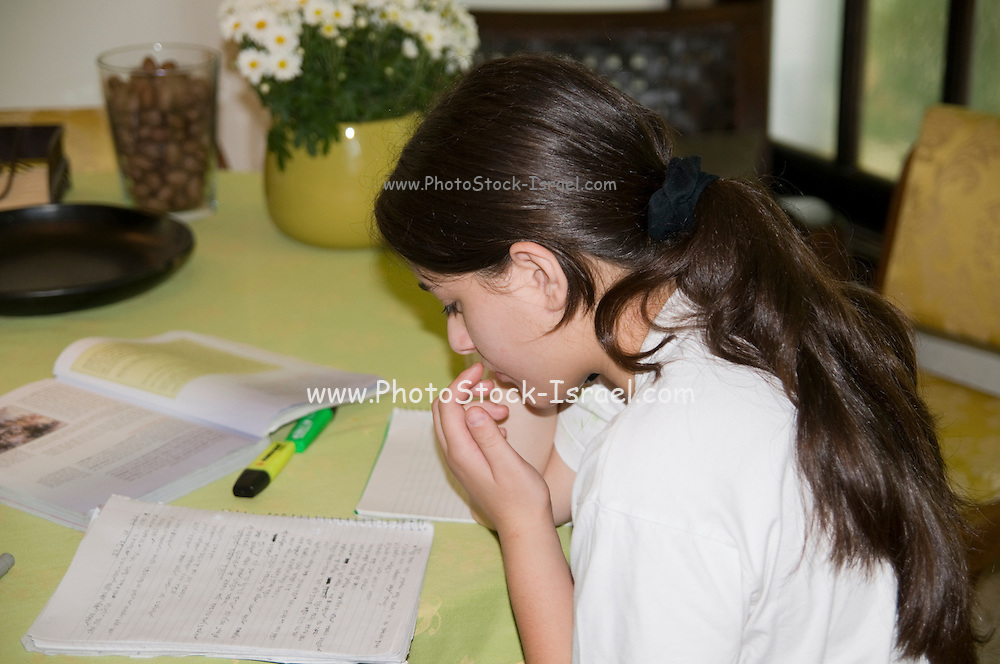 Young female teen of 14 studying and doing homework. Model release available