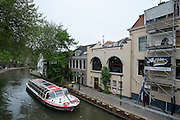 Een rondvaartboot vaart over de Oudegracht in Utrecht langs een steiger waar een gedicht op een gebouw wordt geplaatst.<br /> <br /> A cruise boat is passing a scaffolding near the Oudegracht in Utrecht where a poem is being written on a wall.
