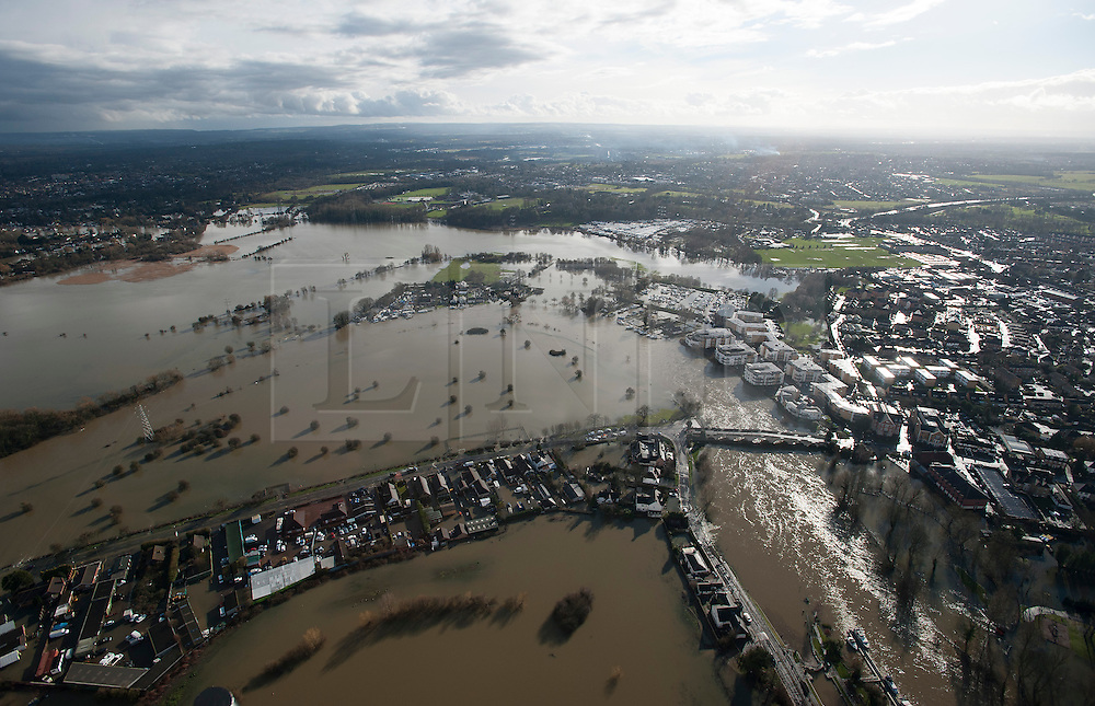 © London News Pictures. 09/02/2014. Chertsey, UK.  Aerial view showing flooding covering Chertsey, Surrey with Chertsey bridge on the left. The Thames river has hit record levels causing extensive flooding to parts of the southeast of England. Photo credit : Ben Cawthra/LNP