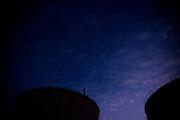 silueta funcionario arriba de un estanque en planta maipú. fumando espero. Copec, 80 años. Santiago de Chile. {date} (©Alvaro de la Fuente/Triple.cl)