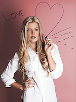 Blonde woman with marker pen drawing hearts
