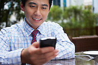 Business man text messaging sitting in outdoor cafe close up