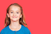 Portrait of young girl smiling against red background