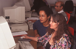 Female teacher and students in adult education computer class,