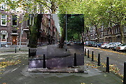 Have I got views for loo! Artist camouflages public toilets and other ugly structures so they're hidden against their backgrounds<br /> <br /> An artist has transformed ugly run-down public structures into works of art by camouflaging them into their background using paint.<br /> Dutch designer Roeland Otten has used mosaics, geometric paint designs, and high resolution photograph wall coverings to recreate the otherwise blocked and lost views of the city streets.<br /> He has managed to turn an air quality measuring station, an electricity substation and a public toilet in Amsterdam into artistic creations.<br /> His aim is to disguise eyesores on picturesque urban streets and pathways and rejuvenate the area by doing so.<br /> <br /> His City Camouflage project, featured in Dezeen magazine, includes a pixelated view of Jan van Galenstraat shopping street in Amsterdam using tiles.<br /> Otten's project began in 2009 with the transformation of a former electricity substation on the corner of Graaf Floristraat and Heemraadsingel in Rotterdam.<br /> <br /> He decorated the building in sheets of aluminium printed with high-resolution photographs of the surrounding streets, so that it seemed almost invisible among the houses and trees.<br /> Last year he used acrylic paint to transform a rusty electricity substation on the Boompjeskade waterfront in Rotterdam.<br /> The bold graphic paintwork makes the substation blend in with the water and foliage nearby.<br /> An old public toilet building used to measure the quality of the air was used for another part of the project, which you can find out more about at www.roelandotten.com.<br /> ©exclusivepix