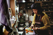 Sayo Ukita prepares fresh vegetables for dinner. Kodaira City, Japan. Material World Project. The Ukita family lives in a 1421 square foot wooden frame house in a suburb northwest of Tokyo called Kodaira City.