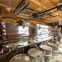 Stainless steel barrels that are used to store and transport maple syrup sit in front of one of the sap boilers at the LaRiviere family syrup operation in Big Six Township, Maine.