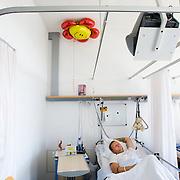 Nederland Rotterdam  31-08-2009 20090831 Foto: David Rozing .Serie over zorgsector, Ikazia Ziekenhuis Rotterdam, afdeling cardiologie. Jonge man in ziekenhuisbed, rust uit. Aan zijn bed hangt een ballon met daarop een smiley, in zijn handgreep zit een knuffelbeertje met de tekst beterschap. Young heartpatient resting in bed, a smiley balloon at his side and a little teddybear saying get well on his bed. ..Foto: David Rozing ..Holland, The Netherlands, dutch, Pays Bas, Europe, op zaal liggen, knuffels, knuffelbeesten,, moral support, blijk van affectie, steuntje in de rug,  overzicht, general view, steunbetuiging, kop ophouden, postitief blijven, posititviteit, moeilijke tijden,copy space, ruimte voor tekst, smiley, smile, lachen, stilleven, still,,ziektekosten,zorgverlening,gedeelde kamer, room, moe, tired, het zwaar hebben