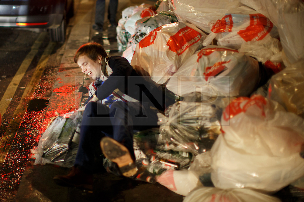"""© licensed to London News Pictures. London, UK 14/12/2013. A """"Mad Friday"""" reveller falls on some bin bags in Soho, London whilst enjoying the last Friday night out before Christmas, which is also the busiest night of the year for emergency services. Photo credit: Tolga Akmen/LNP"""