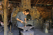 Mathieu Bonnemaison, a blacksmith, at work hammering and shaping metal on an anvil in the forge at the Chateau de Guedelon, a castle built since 1997 using only medieval materials and processes, photographed in 2017, in Treigny, Yonne, Burgundy, France. In the forge, the site's blacksmiths repair and manufacture all the metalwork needed for the project, including chisels, axes, adzes, gates and hinges. The Guedelon project was begun in 1997 by Michel Guyot, owner of the nearby Chateau de Saint-Fargeau, with architect Jacques Moulin. It is an educational and scientific project with the aim of understanding medieval building techniques and the chateau should be completed in the 2020s. Picture by Manuel Cohen