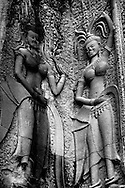 These two Apsara's were located in the inner gate of the Angkor Wat temple complex where nearly 2000 Apsara carvings adorn the walls throughout the temple and represent some of the finest examples of Apsara carvings in Angkorian era art.<br /> <br /> Angkor Wat was built for the king Suryavarman II in the early 12th century as his state temple and capital city.<br /> <br /> It is a massive three-tiered pyramid crowned by five lotus-like towers rising 65 meters from ground level is surrounded by a moat and an exterior wall. All the walls of the temple are covered inside and out with bas-reliefs and carvings. <br /> <br /> Angkor Wat has become a symbol of Cambodia, appearing on its national flag and is worthy of all it's attention. The ruins of Angkor, a UNESCO World Heritage Site with temples numbering over 1000, are hidden amongst forests and farmland to the north of the Tonle Sap Lake outside the modern city of Siem Reap, Cambodia.