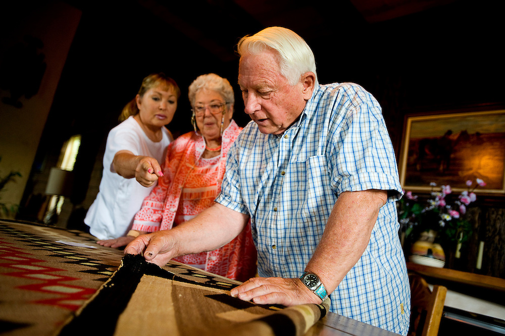 081910     Brian Leddy.Martin Link examines a Navajo rug as Carmen Mirabel-Acosta, the owner of the rug, and her daughter, Holly Acosta-Gray stand by on Aug. 13. Mirabel-Acosta recently found the rug in her attic and has donated it to the Gallup Cultural Center.
