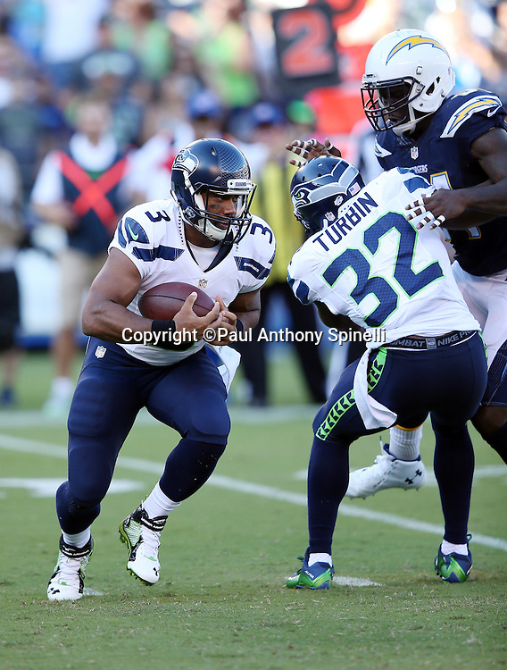 Seattle Seahawks quarterback Russell Wilson (3) gets a block by Seattle Seahawks running back Robert Turbin (32) as he looks for running room in the first quarter during the 2015 NFL preseason football game against the San Diego Chargers on Saturday, Aug. 29, 2015 in San Diego. The Seahawks won the game 16-15. (©Paul Anthony Spinelli)