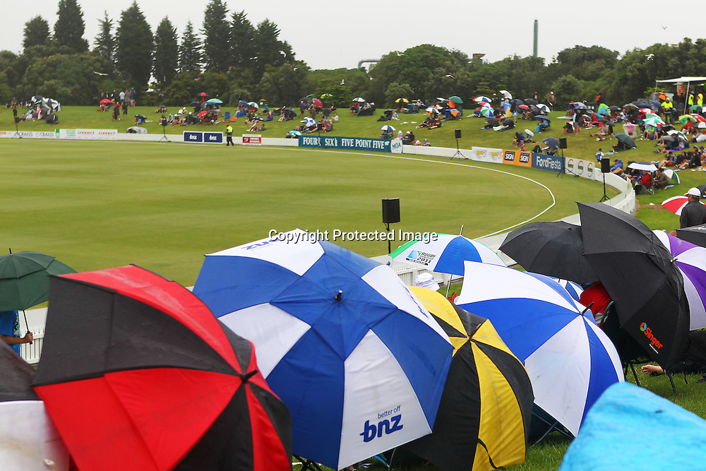 Spectators take shelter from the rain during the HRV Cup match between the Northern Knight v Wellington Firebirds. Men's domestic one day cricket. Blake Park, Mt Maunganui, New Zealand. 4 January 2012. Ella Brockelsby / photosport.co.nz