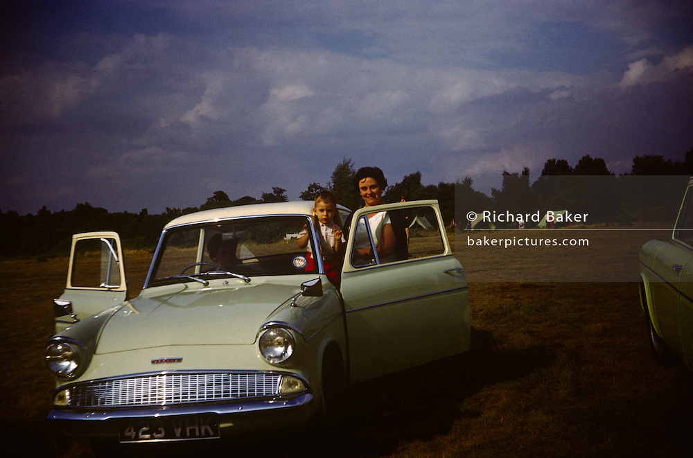 A mother holds her 4 year-old son with the family Ford Anglia during summer time in the early 1960s. There are tents behind them in the distance, a summer camping site in Essex. Both doors of the car are open for this portrait, a summer's day in an era of innocence when car ownership was still to become popular among the working and middle-classes is estates like this. The colours are brillianty reproduced and was recorded on a film camera by the child's father, an amateur photographer in 1962. The picture shows us a memory of nostalgia in an era from the last century.