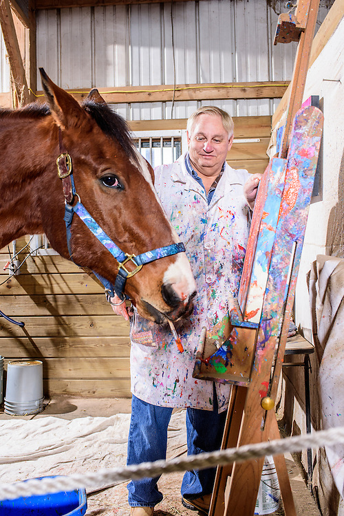 Gettysburg, Pennsylvania - February 06, 2017: Ron Krajewski assists Metro Meteor with his paintings in the studio space adjacent to the the retired racehorse's stall at the Rickety Bridge Farm in Gettysburg, Pa.<br /> <br /> Knee injuries put Metro Meteor in an early retirement, and left him unridable as a pleasure horse. Noticing his horse's affinity for head bobbing, he put a paint brush in his mouth and canvas in front. Metro Meteor's  paintings sold. Painting helped save his life, and helped save other horses' lives, too. Half the money from his paintings goes to New Vocations Racehorse Adoption Program and Gentle Giants Draft Horse Rescue.<br /> <br /> <br /> CREDIT: Matt Roth