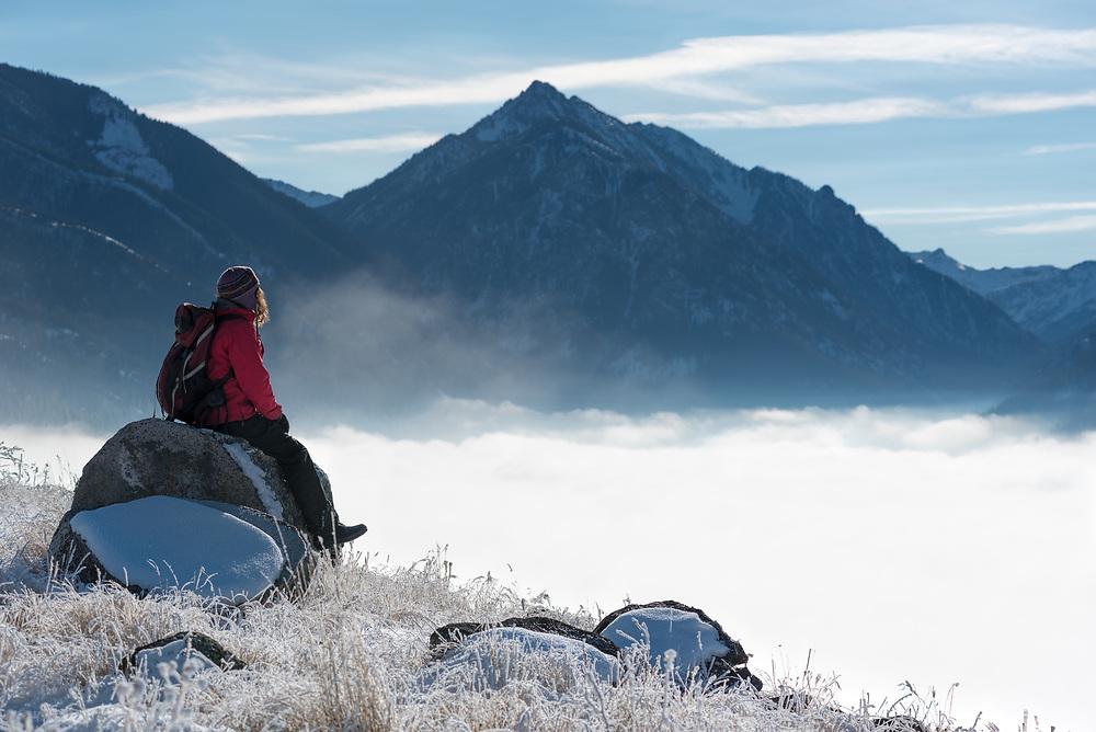 Hiker gazing on Wallowa Lake's east moraine gazing out at the Wallowa Mountains and fog filling the lake basin, Oregon.