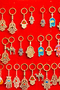 FEZ, MOROCCO - 3rd DECEMBER 2016 - Close-up of decorative key rings and key chains hanging for sale on a red background in the souks of the old Fez Medina, Middle Atlas Mountains, Morocco.