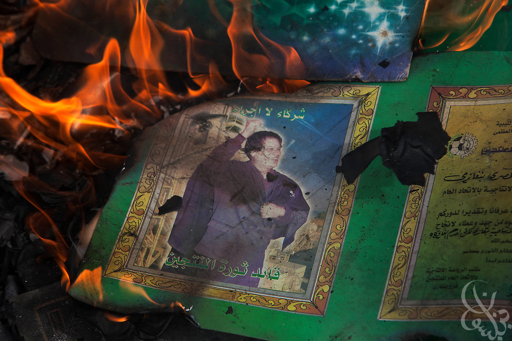 An image of Libyan leader Col. Muammar el-Qaddafi is seen alight in a burning pile of books and posters during a protest in the eastern city of Benghazi, Libya March 02, 2011. March 02 is traditionally a celebration of the People's Authority Day in Libya, and protesters marked the occasion by burning Qaddafi books, speeches and images. .Slug: Libya.Credit: Scott Nelson for the New York Times