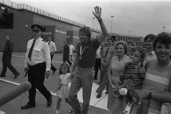 1983-15-08.15th August 1983.15-08-1983.08-15-83..Photographed at Dublin Airport..A Golden moment:..Gold medalist Eamonn Coughlan geeeted by press and supporters on the tarmac of Dublin Airport on his return from the World Athletic Championships in Finland. His wife Yvonne and chldren Suzanne (four) and Eamonn Jn (two) are with him. Suzanne walks hand in hand with her dad while his wife holds Eamonn Jn. His mother Kathleen  walks beside him.