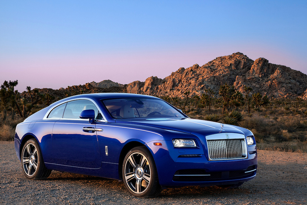 2015 Rolls Royce Wraith, Salamanca Blue.  Photographed in Joshua Tree, CA. 3/4 side view in desert with mountains and trees at sunset.
