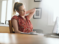 Woman using laptop sitting at dining table low angle view