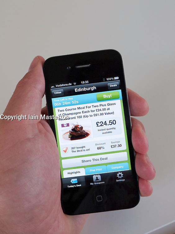 Using Groupon app to search for deals on iPhone 4G smart phone