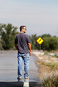 WIGGINS, CO - SEPTEMBER 14: Bill Dinis of Wiggins, Colorado walks up to the edge of flood waters from the South Platte River as it washes over Morgan County Road 1 near Wiggins as heavy rains for the better part of week fueled widespread flooding in numerous Colorado towns on September 14, 2013. (Photo by Marc Piscotty/ © 2013)