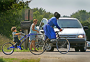 An Amish woman and a child on a bike catch the curious eye of a motorist along Porter Road near Bonduel last weekend. JEFFREY PHELPS