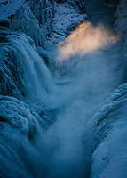 Gullfoss waterfall in winter. Golden spray above falls. South Iceland.