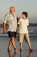Boy and grandfather walking on beach at dusk