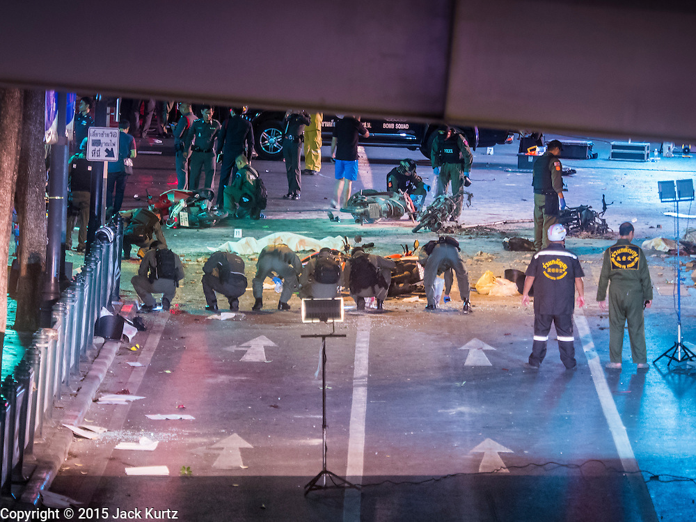 17 AUGUST 2015 - BANGKOK, THAILAND: Thai police scour the street in front of Erawan Shrine for evidence after a large explosion at the shrine. An explosion at Erawan Shrine, a popular tourist attraction and important religious shrine, in the heart of the Bangkok shopping district killed at least 19 people and injured more than 120 others, mostly foreign tourists, during the Monday evening rush hour. Twelve of the dead were killed at the scene. Thai police said an Improvised Explosive Device (IED) was detonated at 18.55. Police said the bomb was made of more than six pounds of TNT stuffed in a pipe and wrapped with white cloth. Its destructive radius was estimated at 100 meters. The Bangkok government announced that public schools would be closed Tuesday as a precaution.         PHOTO BY JACK KURTZ