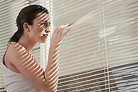 Young woman peering through blinds in home
