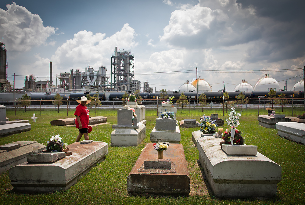 """Protester at the Reveille Town Cemetery in Plaquemine, Louisiana on the fourth day of the Coalition Against Death Alley's 5 day march. The Coalition Against Death Alley (CADA), is a group of Louisiana-based residents and members of various local and state organizations, is calling for a stop to the construction of new petrochemical plants and the passing of stricter regulations on existing industry in the area that include the groups RISE St. James, Justice and Beyond, the Louisiana Bucket Brigade, 350 New Orleans, and the Concerned Citizens of St. John.  Louisiana's Cancer Alley, an 80-mile stretch along the Mississippi River, is also known as the """"Petrochemical Corridor,"""" where there are over 100 petrochemical plants and refineries. The cemetery is located within the fenceline of Westlake Chemical plant that controls acess to it."""