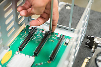 Cropped image of male technician repairing PCI slots in computer factory