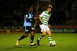 Yeovil Town's Sam Foley keeps the ball well under pressure from Wycombe Wanderers' Ade Azeez - Photo mandatory by-line: Dougie Allward/JMP  - Tel: Mobile:07966 386802 04/12/2012 - SPORT - FOOTBALL - Johnstone's Paint Trophy  -  Yeovil  -  Huish Park  -  Yeovil Town V Wycombe Wanderers