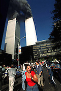 People flee the engulfed World Trade Center Twin Towers prior to collapse after terrorist attacks in Manhattan, NY. 9/11/2001