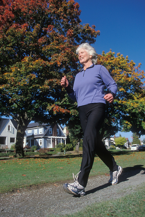 Mature Caucasian Woman Power Walking in a park lined by houses.<br />