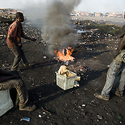 Boys burn parts of computers and other electronics to recover copper wires and cables near the Agbogboloshie market in Accra, Ghana on Thursday August 21, 2008..