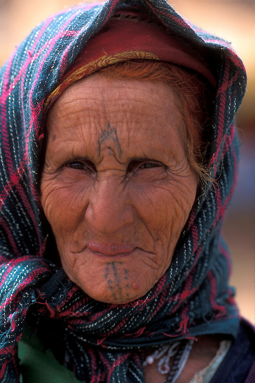 Africa, Morocco, Elderly Berber woman with facial tattoo at country market in Atlas Mountains near village of Ait Pagella