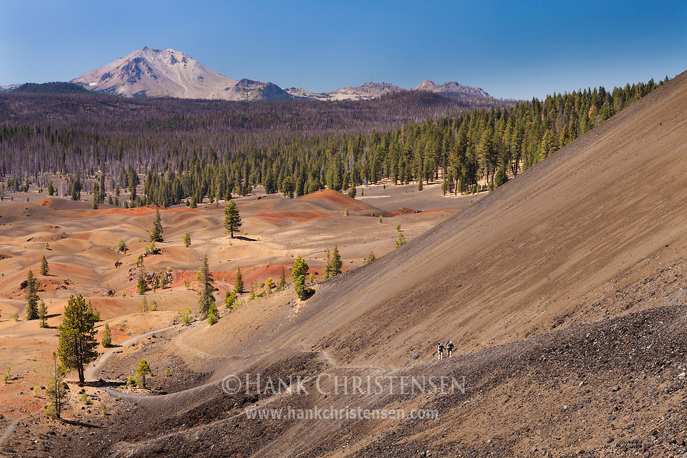 Two backpackers climb the steep southern trail up the Lassen Cinder Cone.  Mt Lassen and the Painted Dunes can be seen to the west.