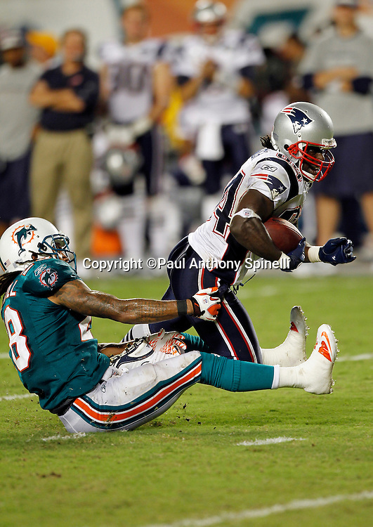 New England Patriots wide receiver Deion Branch (84) catches a third quarter pass good for a first down despite a tackle attempt by Miami Dolphins defensive back Nolan Carroll (28) during the NFL week 1 football game against the Miami Dolphins on Monday, September 12, 2011 in Miami Gardens, Florida. The Patriots won the game 38-24. ©Paul Anthony Spinelli