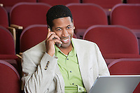 Man sitting in auditorium, using mobile phone and laptop, portrait