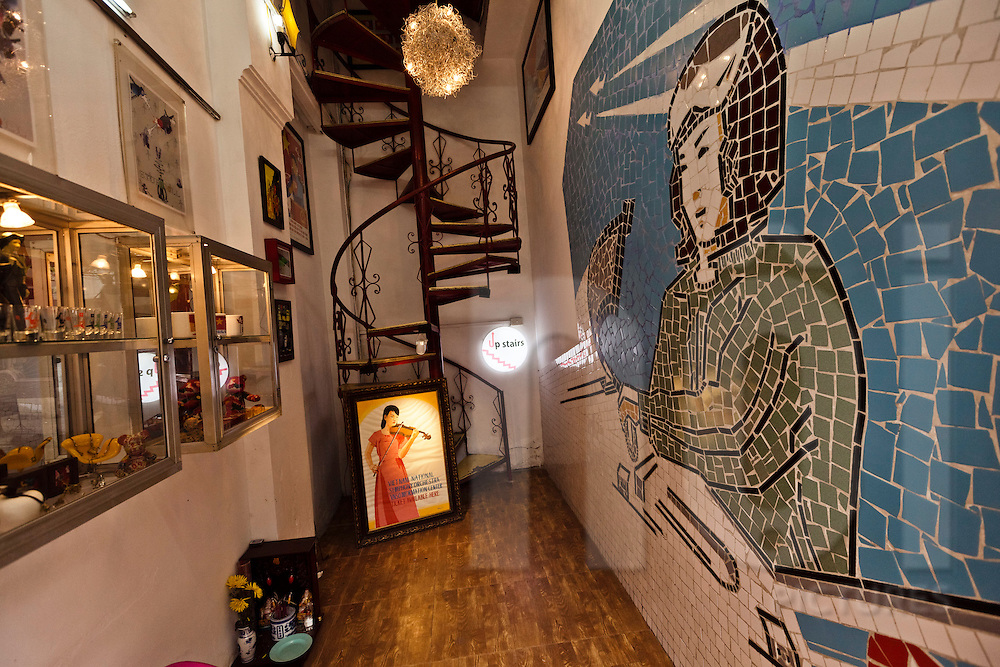 The artfilled narrow entryway of boutique propaganda shop P, with a spiral staircase at the far end, Nha Chung steet, Hanoi, <br /> Vietnam, Southeast Asia