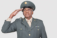 Senior male US military officer saluting over gray background
