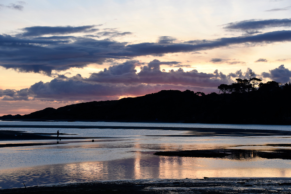 Man fishing at Raglan Beach as the sunset starts to turn pink